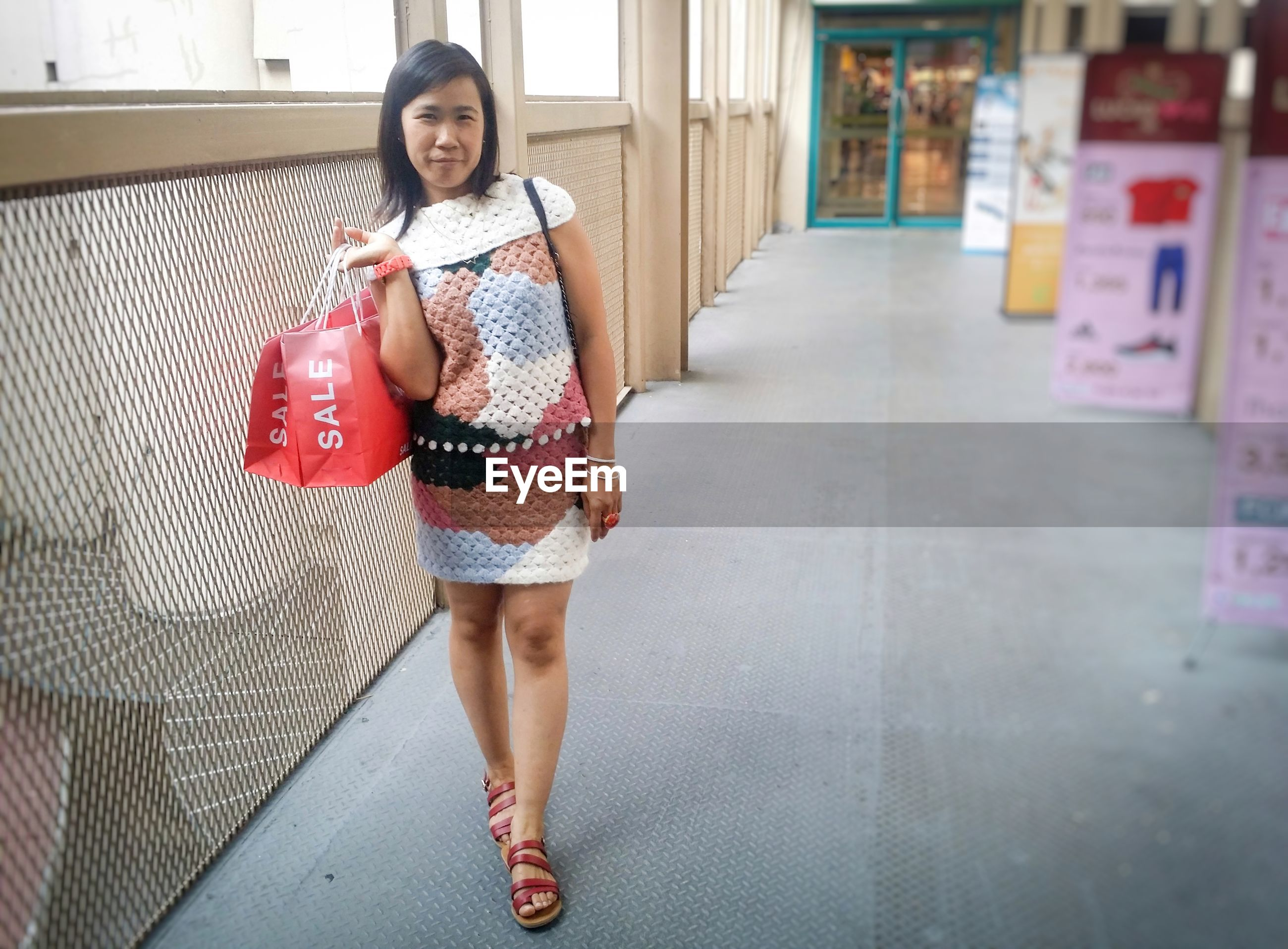 Portrait of woman with shopping bag standing in mall