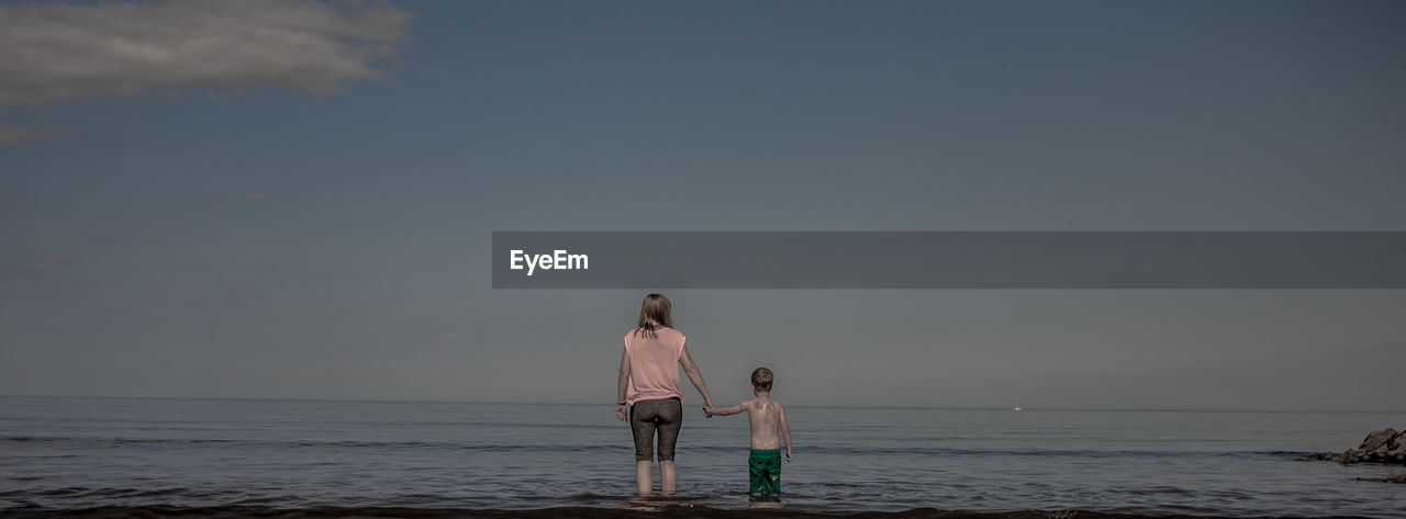 Rear view of mother and son standing in sea against sky at coldingham bay