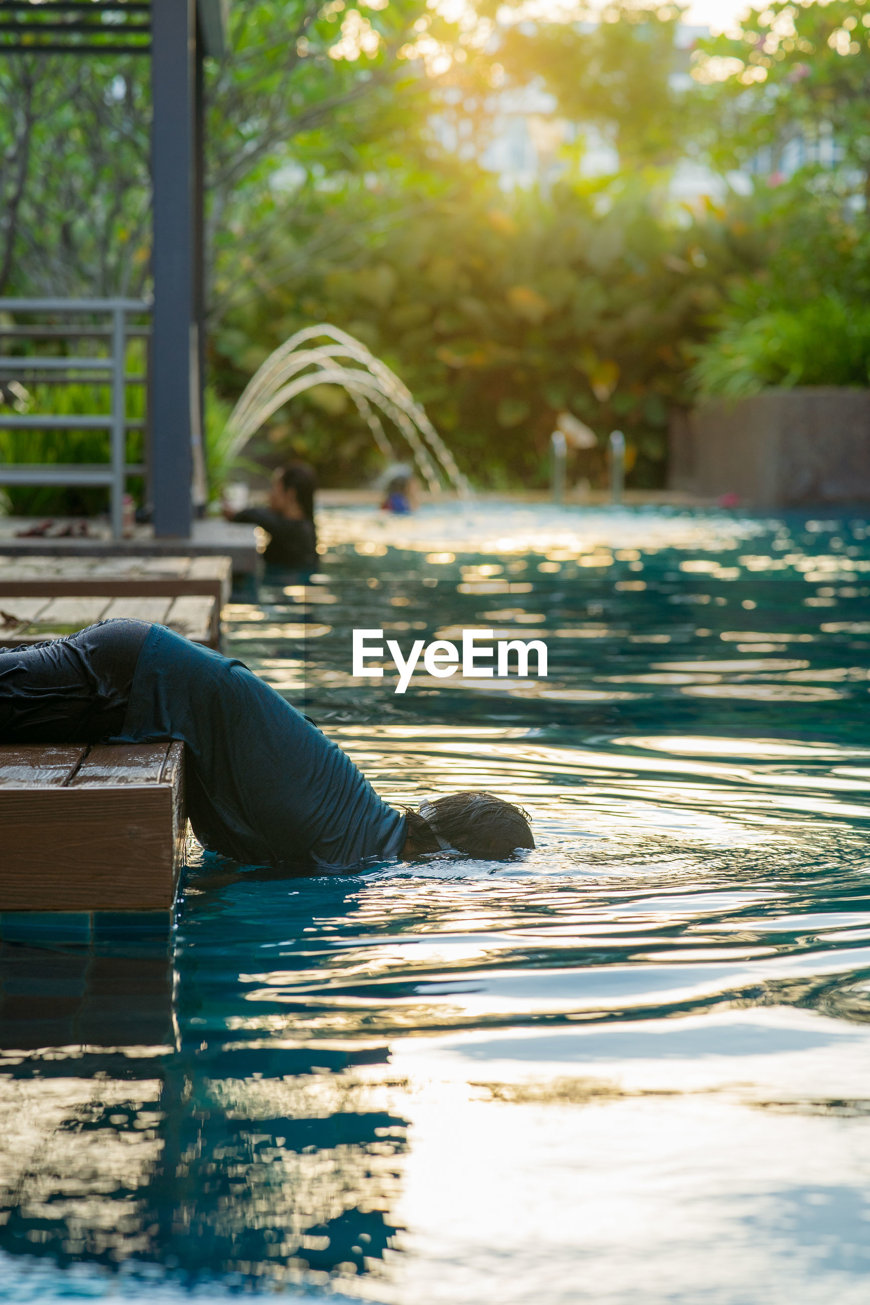SIDE VIEW OF MAN LYING IN SWIMMING POOL