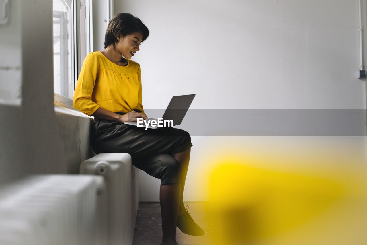 FULL LENGTH OF MAN USING MOBILE PHONE WHILE SITTING IN OFFICE