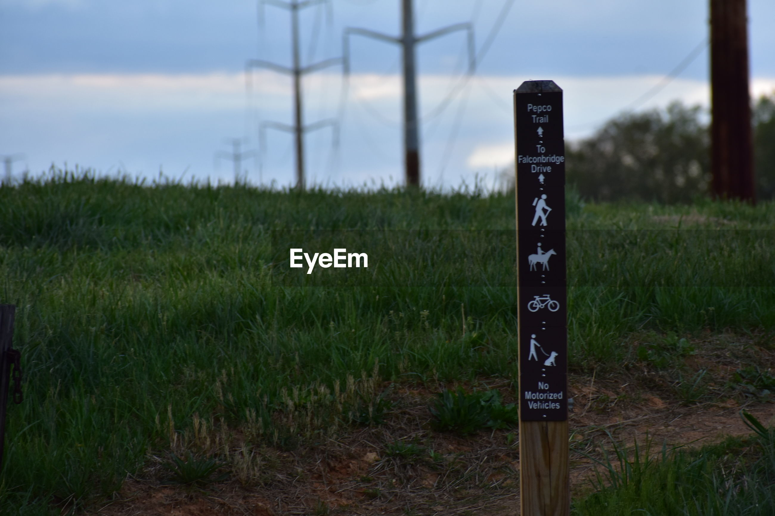 INFORMATION SIGN ON WOODEN POST AT FIELD
