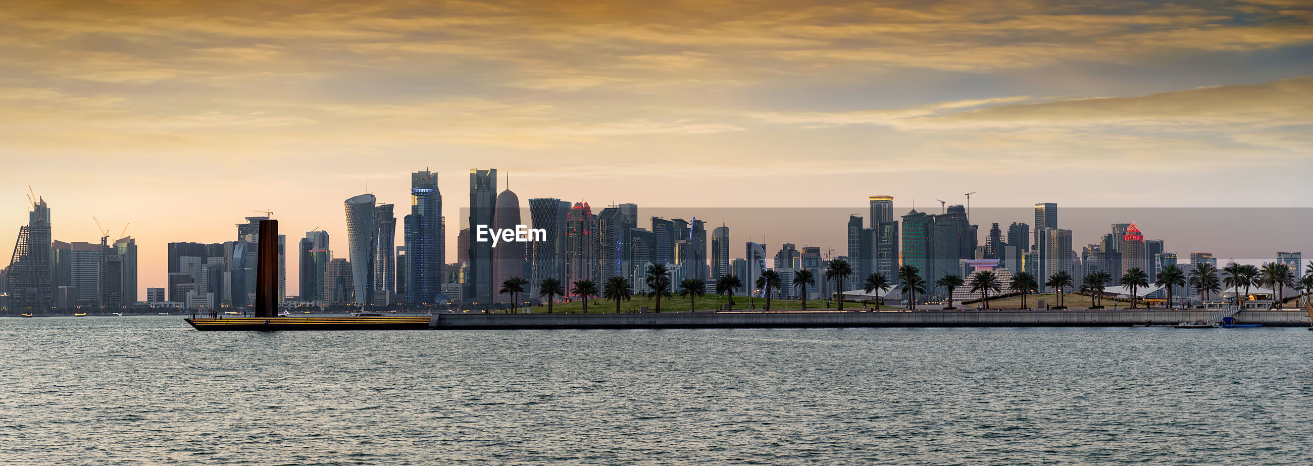Panoramic view of buildings and sea in city during sunset