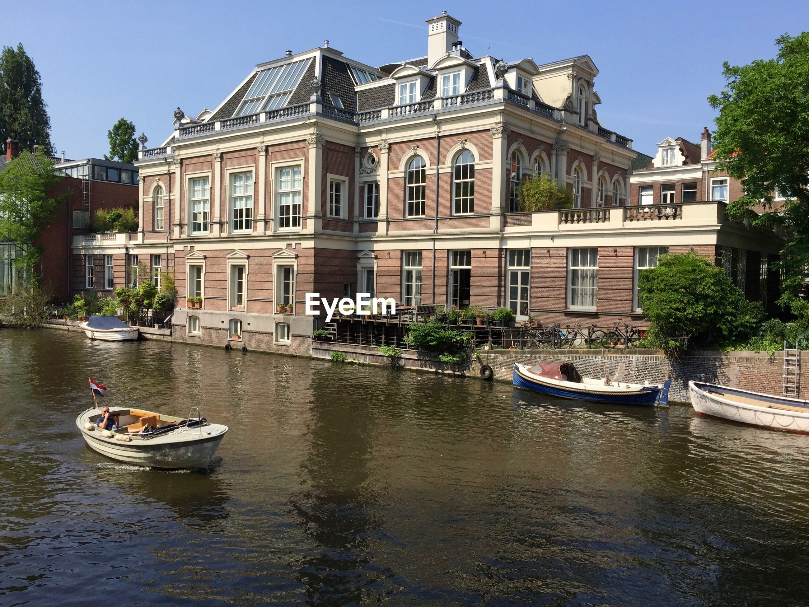 BOATS IN CANAL BY BUILDINGS AGAINST SKY IN CITY