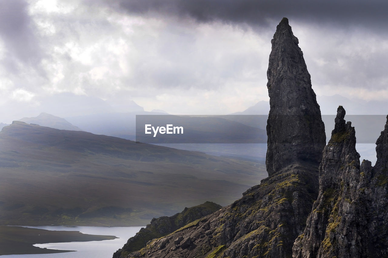 Rock Formations And Mountains Against Cloudy Sky