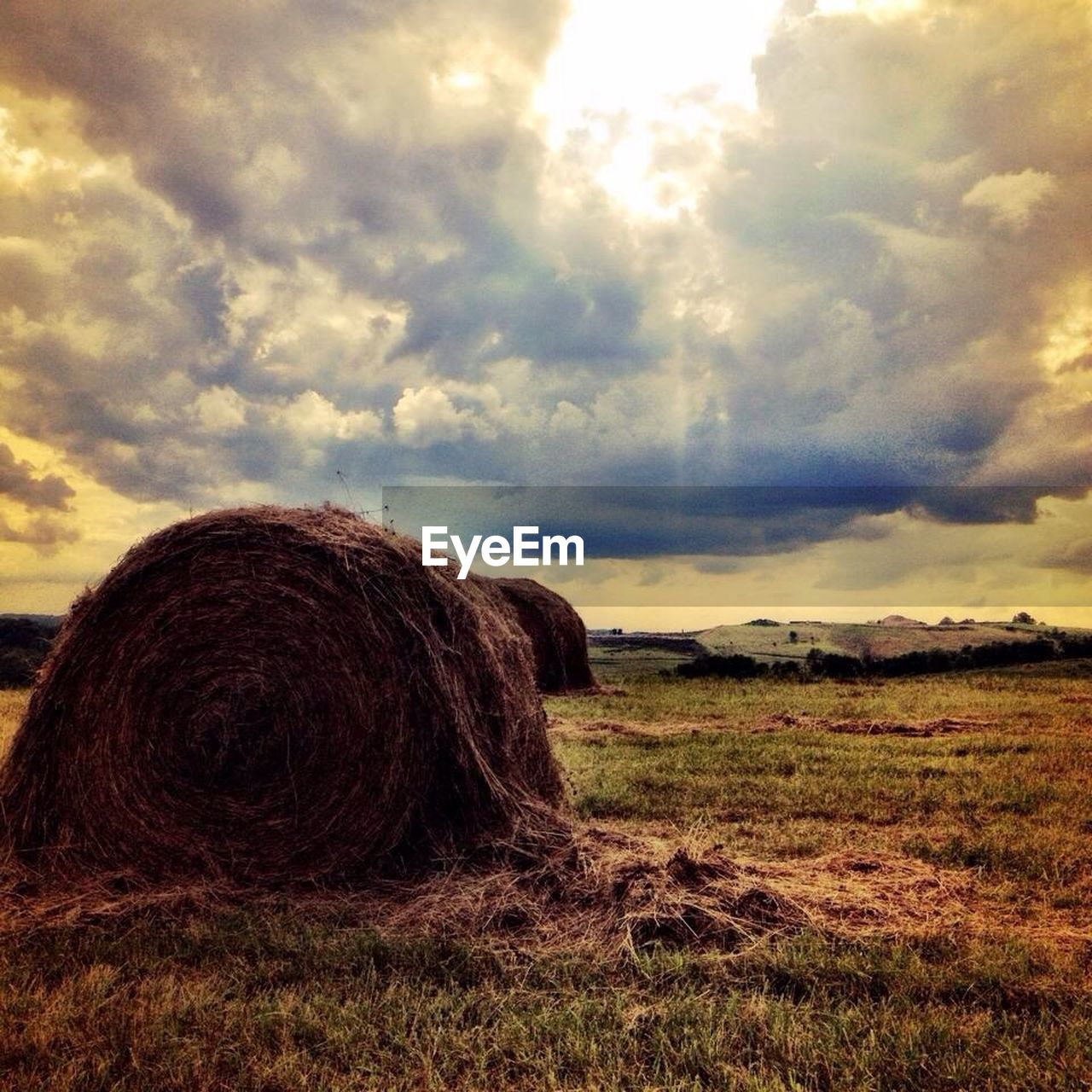 Hay Bales On Grassy Field Against Cloudy Sky