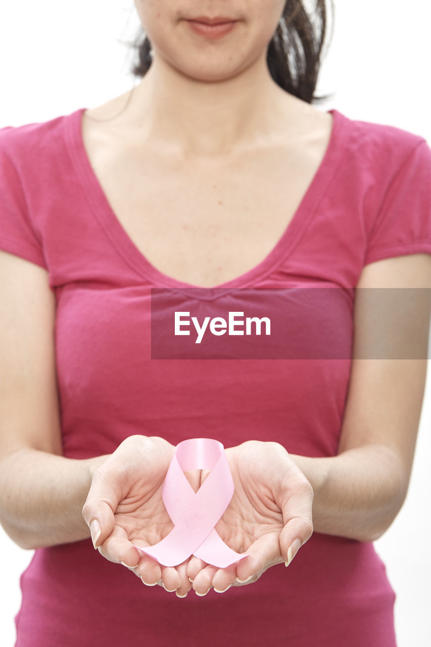 Midsection of woman holding breast cancer awareness ribbon against white background