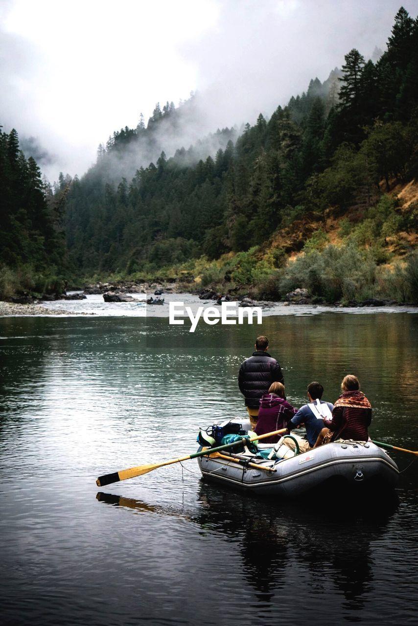 People kayaking on lake against sky