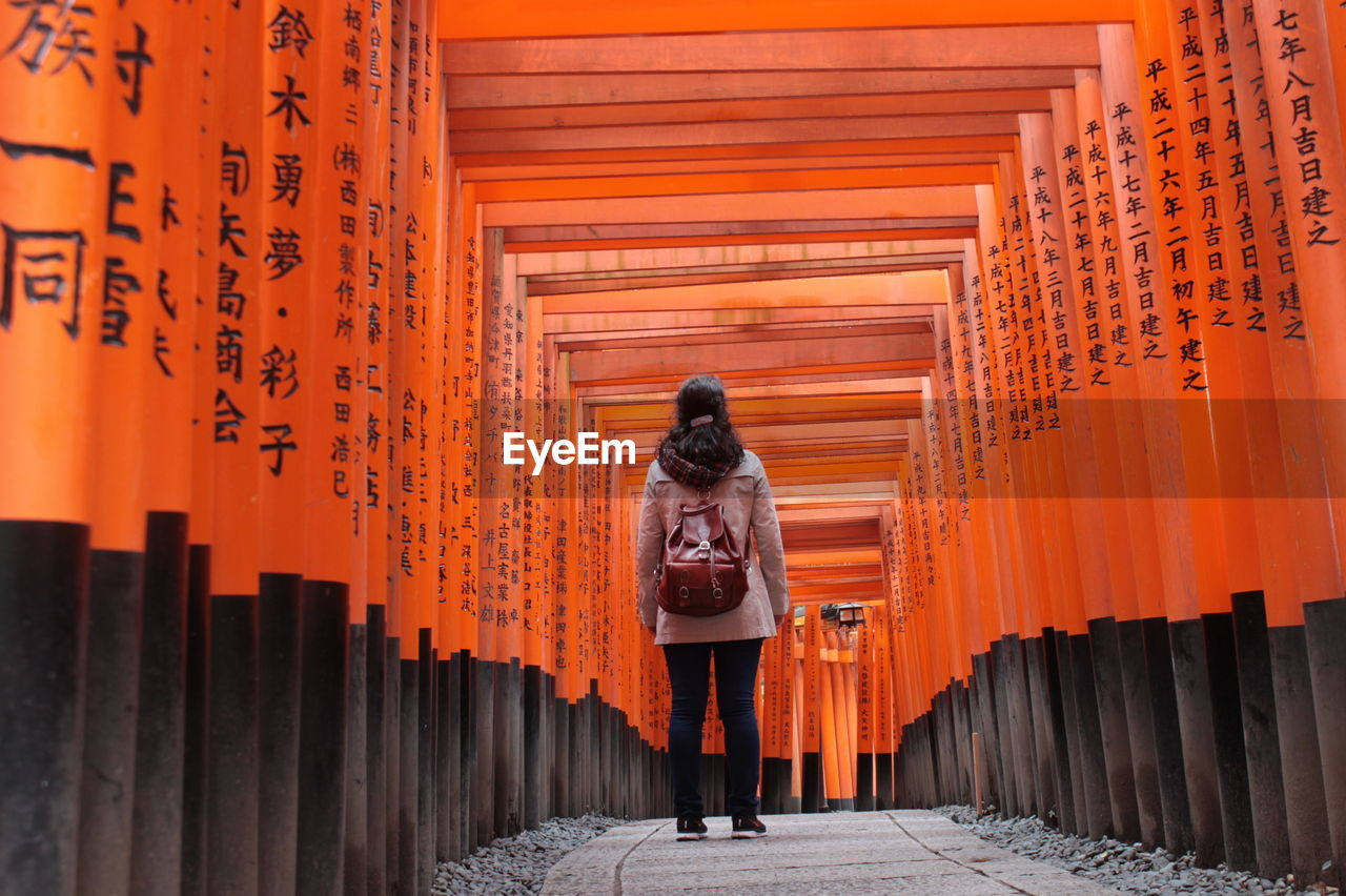 Rear View Of Woman Standing Amidst Torii Gates At Fushimi Inari Shrine