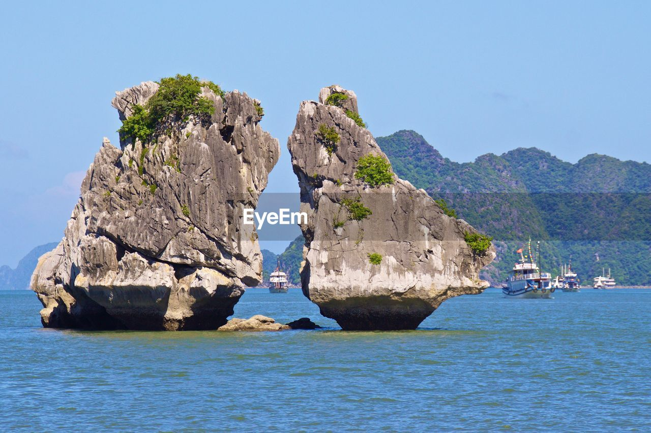 rock - object, rock formation, nature, sea, water, waterfront, beauty in nature, scenics, geology, tranquility, clear sky, tranquil scene, idyllic, day, physical geography, outdoors, sky, no people, blue, mountain