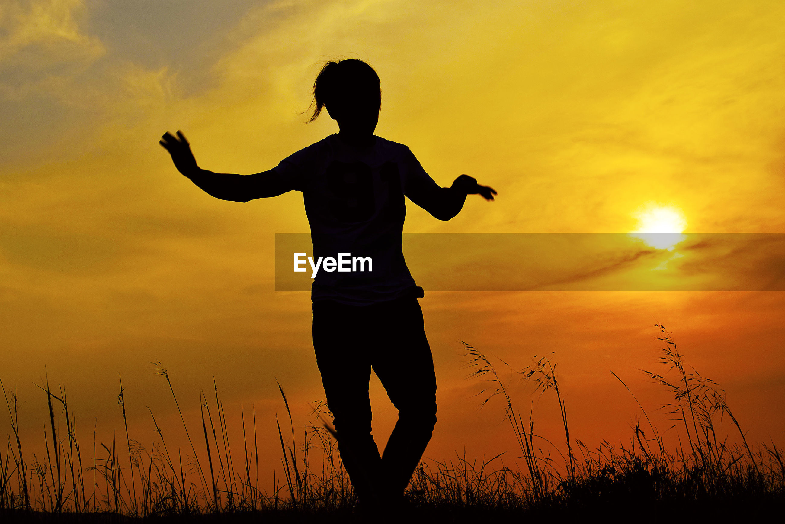 Silhouette woman dancing on land against sky during sunset