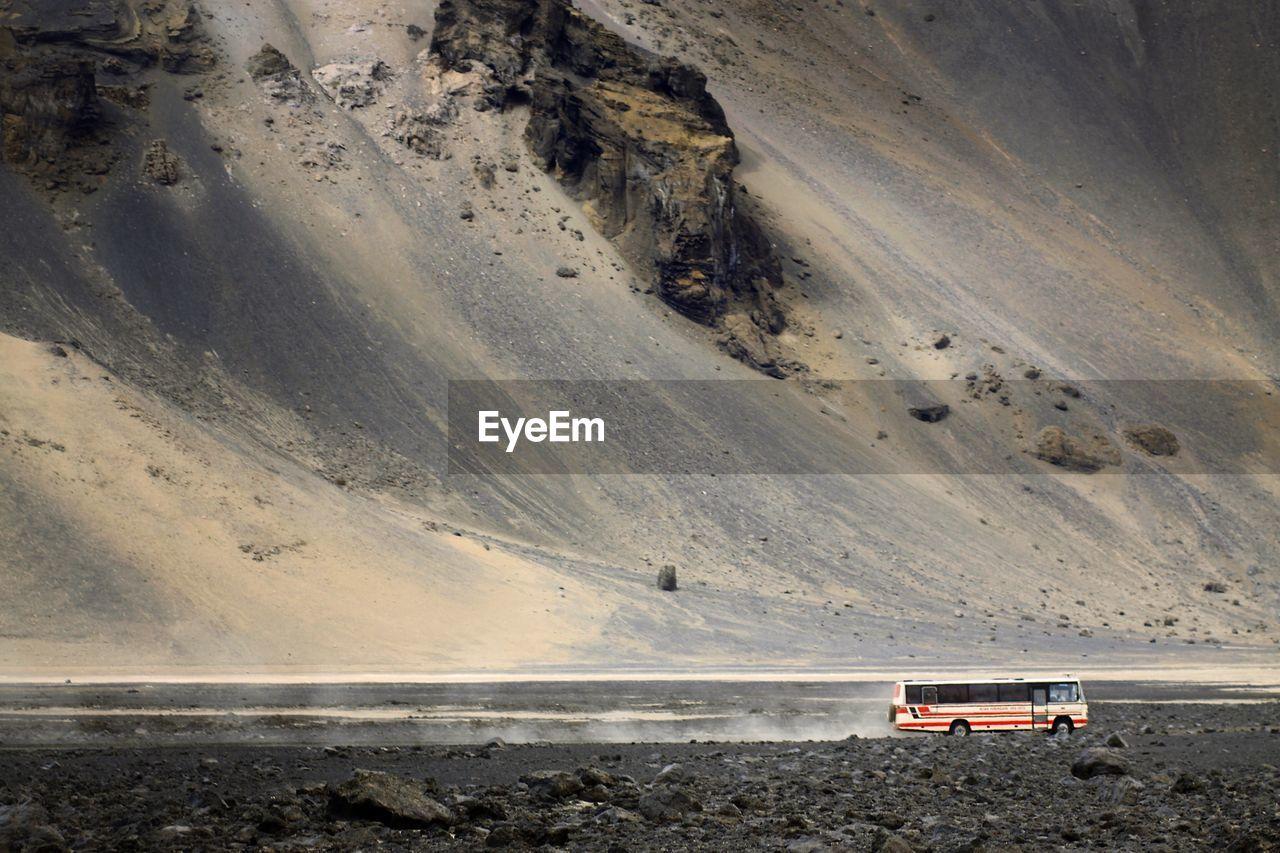 Bus moving in desert against mountain