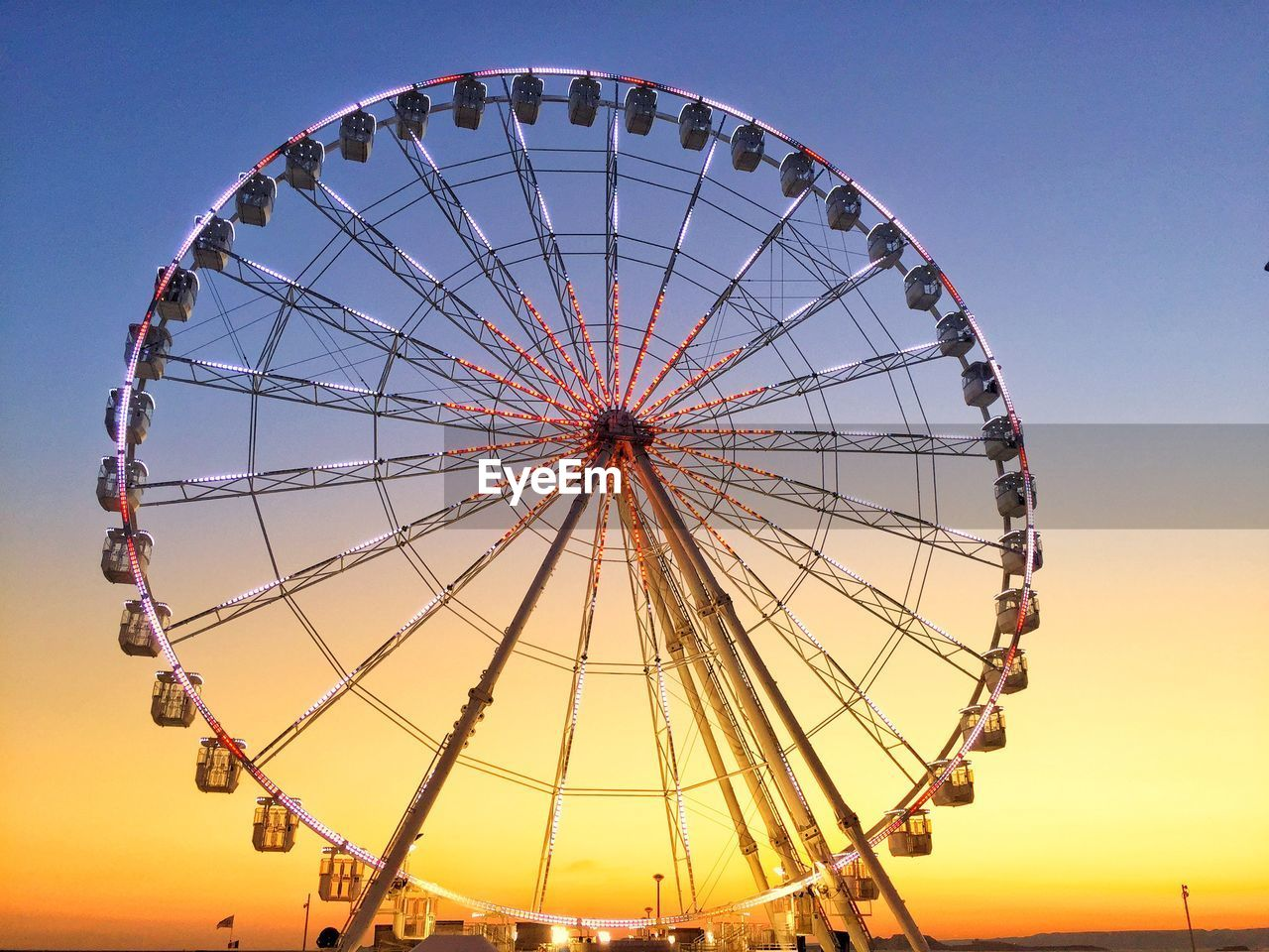 Low Angle View Of Ferris Wheel Against Sky During Sunset