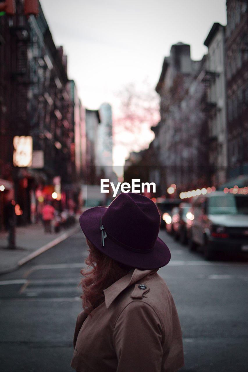 Side View Of Woman Wearing Purple Hat On Street In City