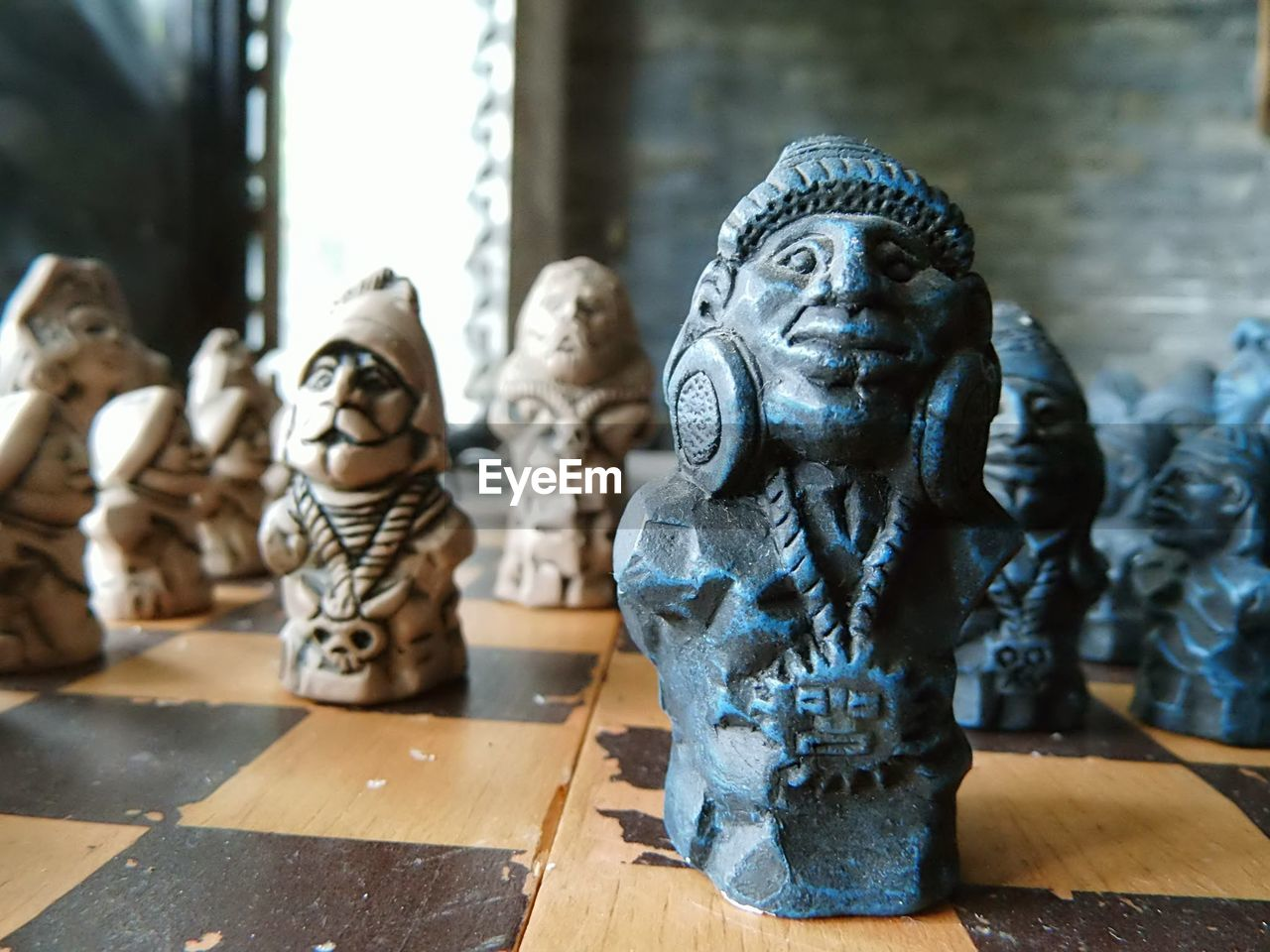 representation, art and craft, human representation, sculpture, creativity, statue, spirituality, religion, male likeness, no people, belief, focus on foreground, craft, indoors, close-up, day, table, wood - material, idol