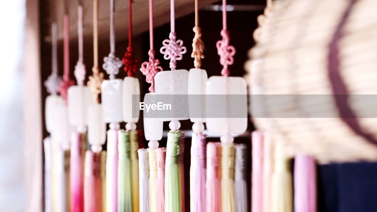 CLOSE-UP OF MULTI COLORED DECORATIONS HANGING IN SHELF