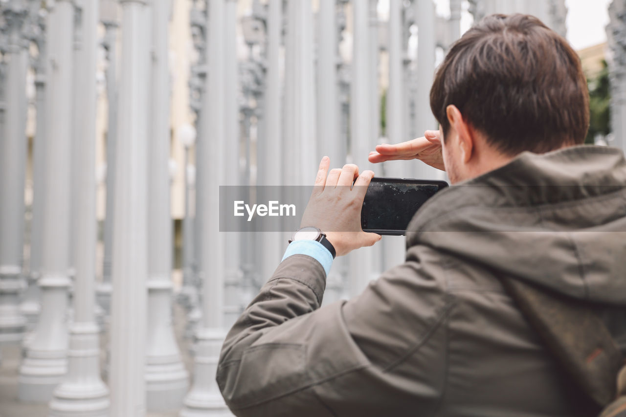Rear View Of Man Photographing Columns Of Urban Lights On Smart Phone