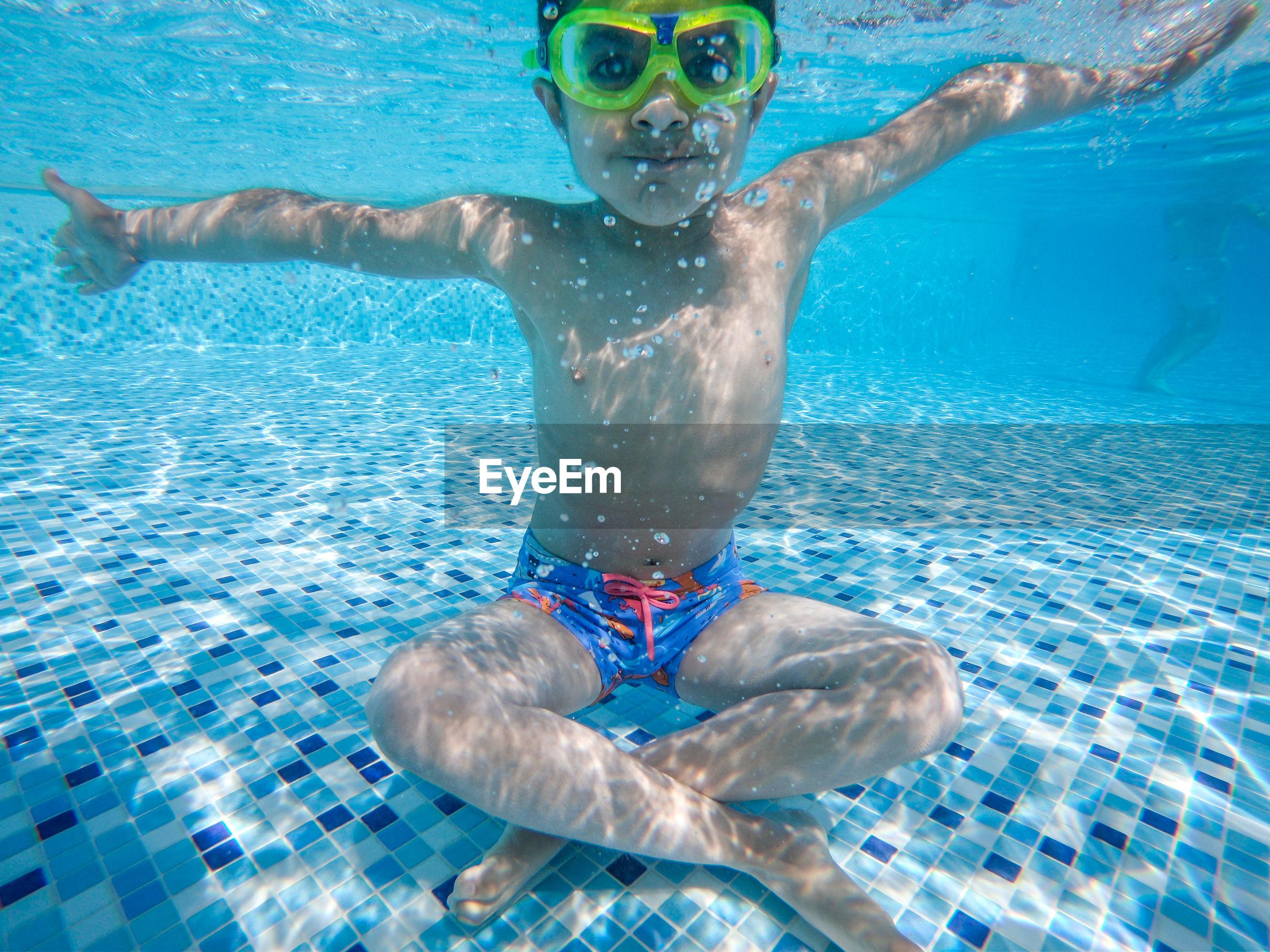 Portrait of boy sitting in swimming pool