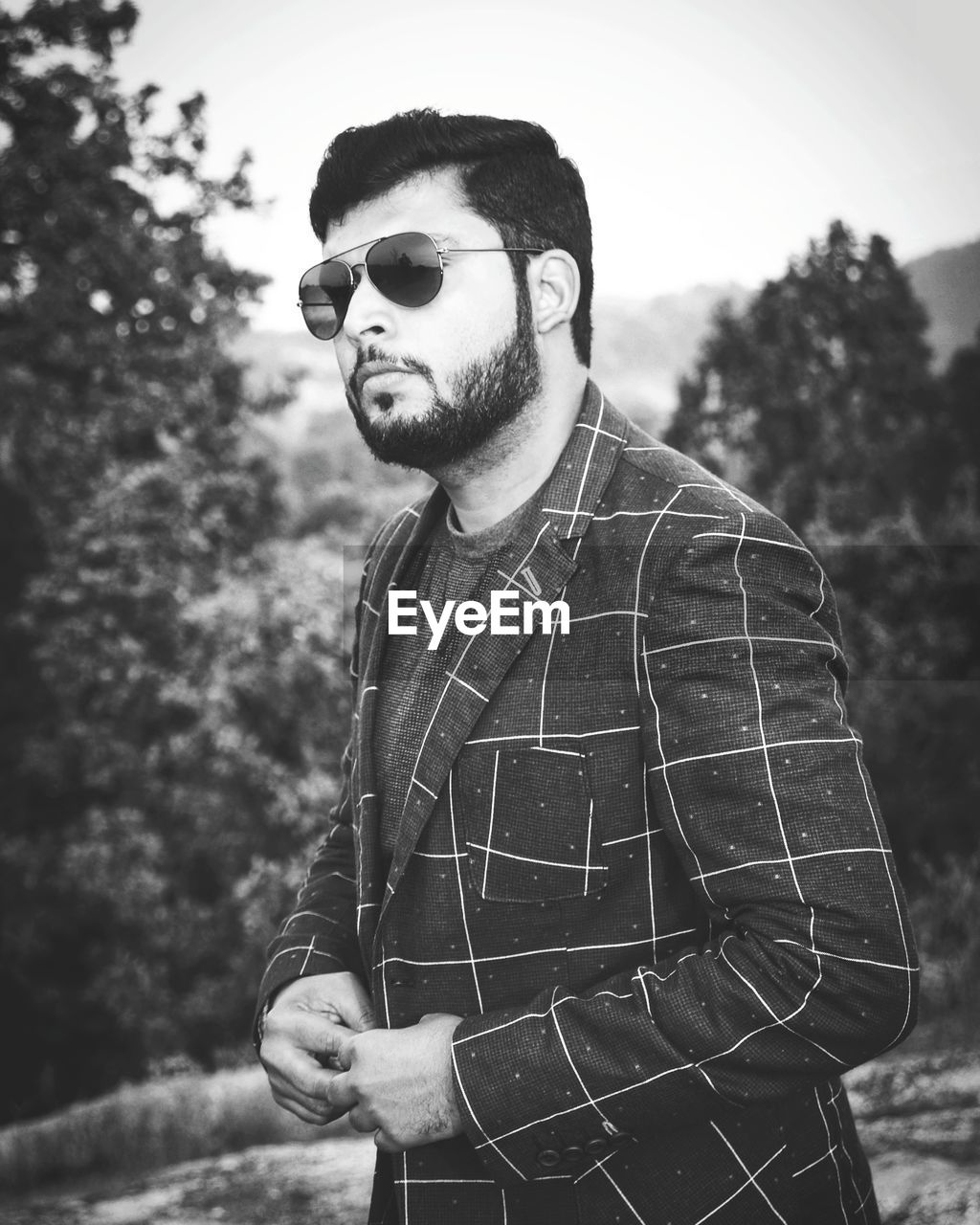 young men, sunglasses, glasses, one person, young adult, fashion, standing, real people, waist up, day, lifestyles, front view, plant, casual clothing, leisure activity, focus on foreground, nature, tree, outdoors