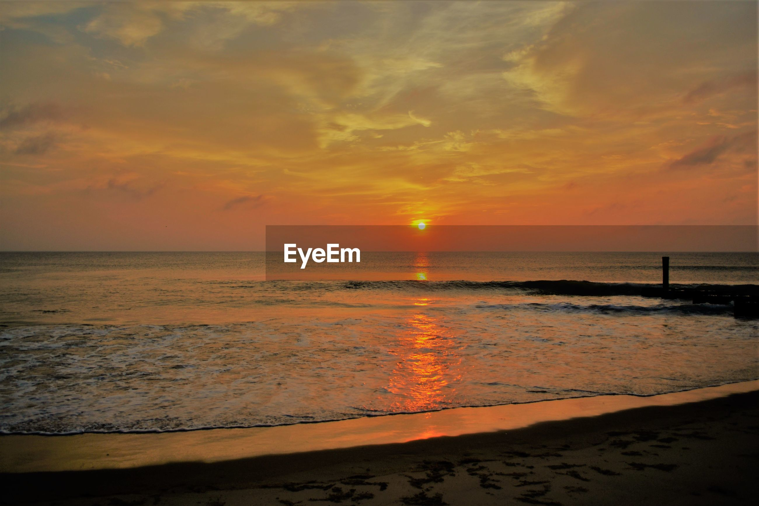 SCENIC VIEW OF SEA AGAINST CLOUDY SKY DURING SUNSET