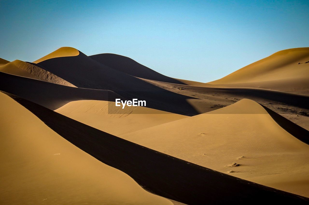 Low Angle View Of Sand Dunes Against Clear Sky