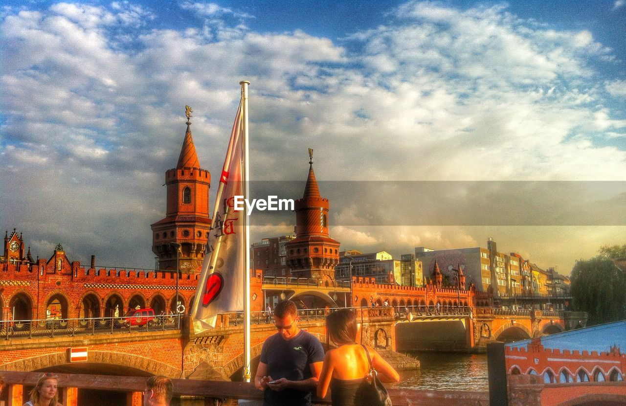 architecture, built structure, sky, cloud - sky, building exterior, water, blurred motion, travel destinations, real people, travel, tourism, city, women, motion, bridge - man made structure, city life, long exposure, large group of people, men, outdoors, lifestyles, day, people