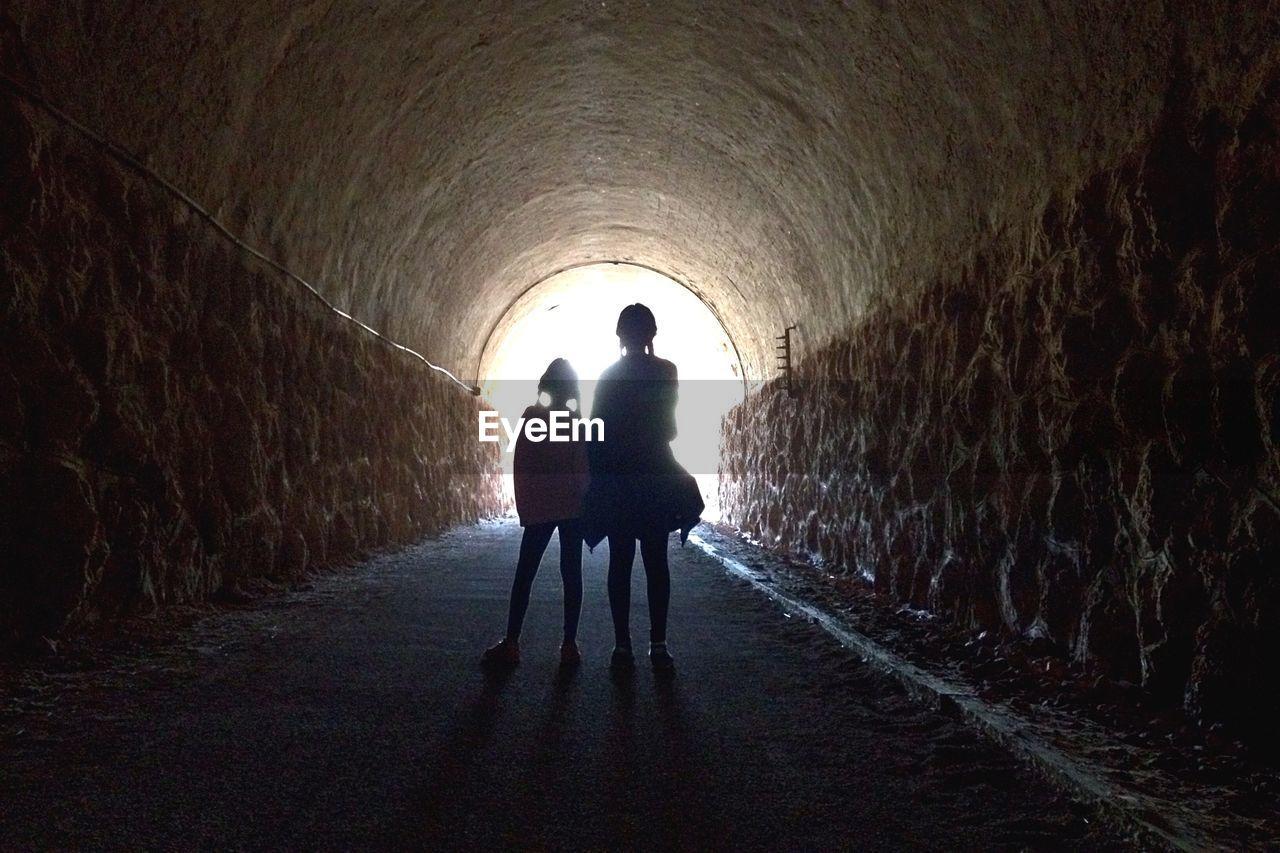 Siblings Standing In Tunnel