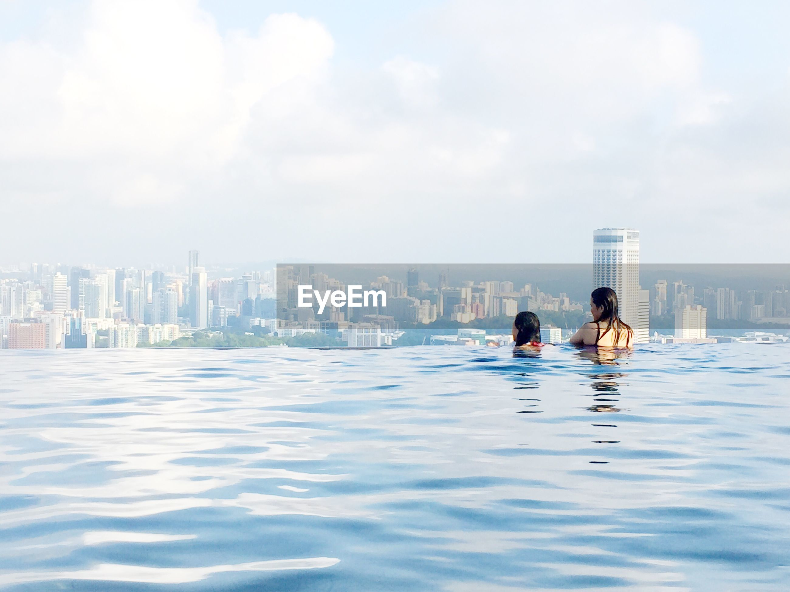 Women looking at view from infinity pool at marina bay sands