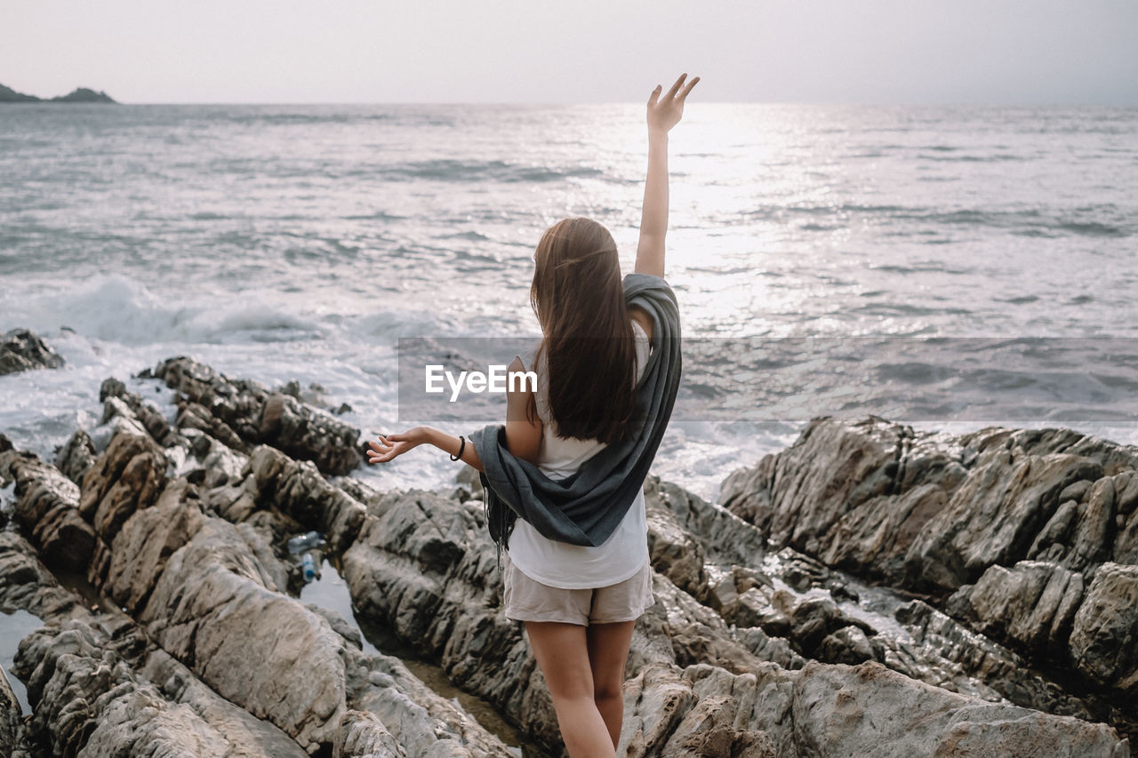 Rear view of woman waving hand while standing on rock by sea against sky