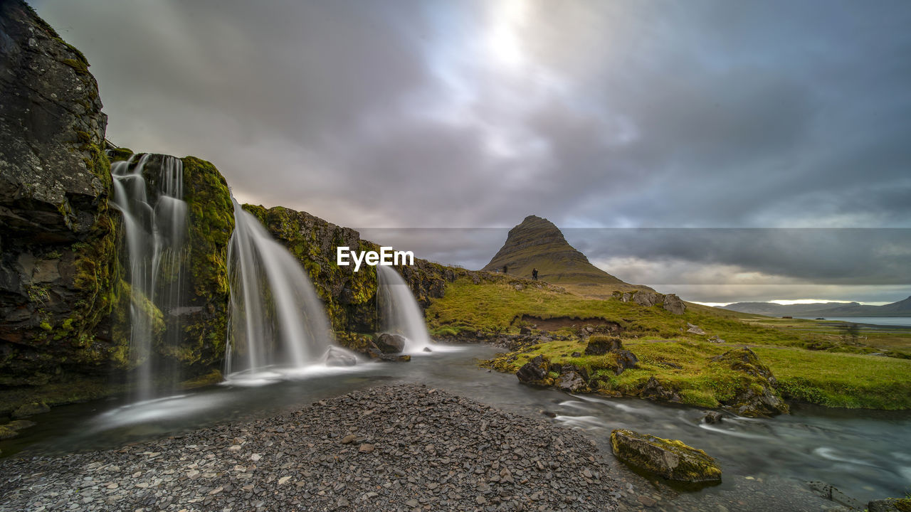 PANORAMIC VIEW OF WATERFALL AGAINST SKY