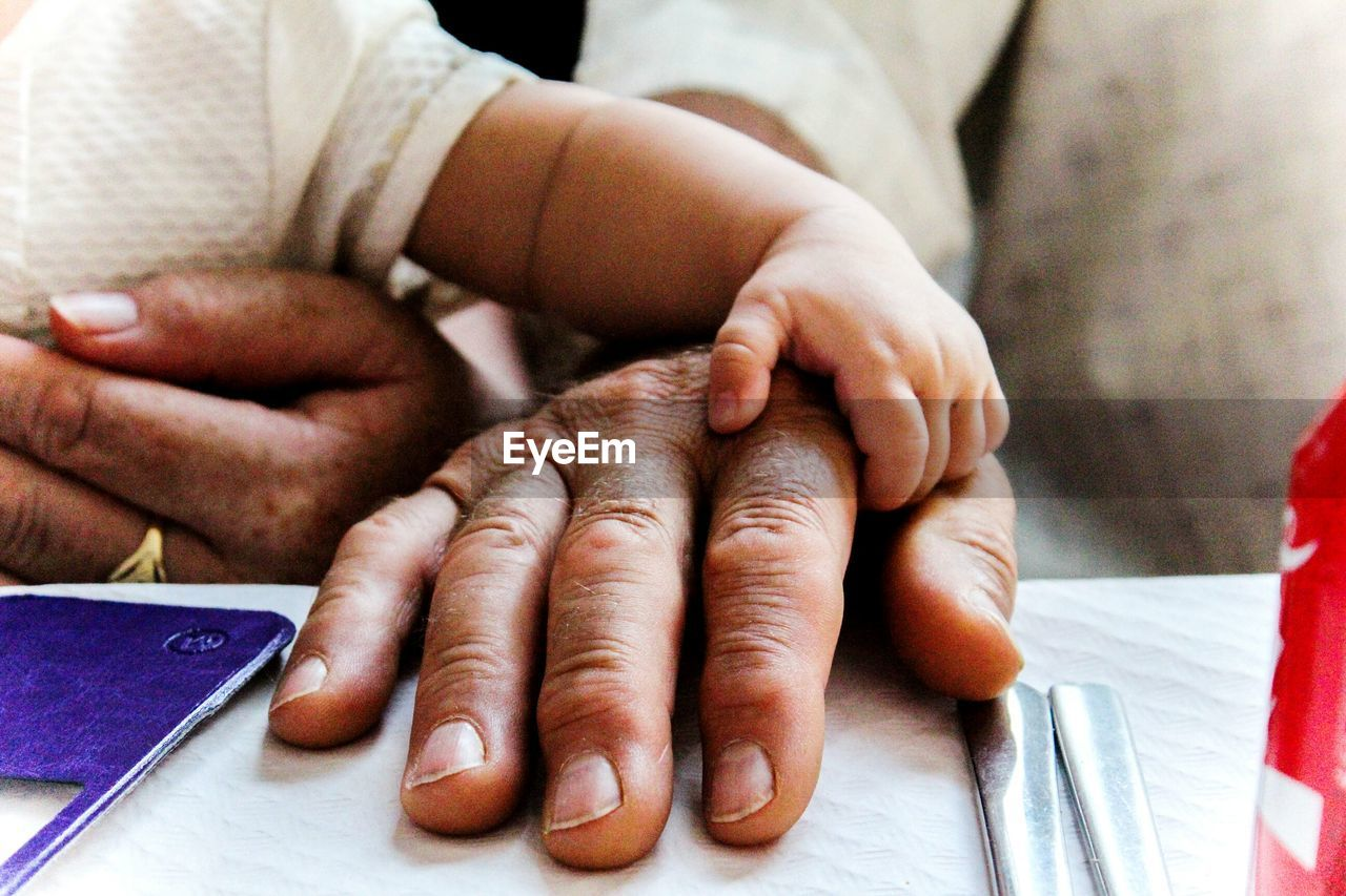 Cropped Hand Of Person With Baby
