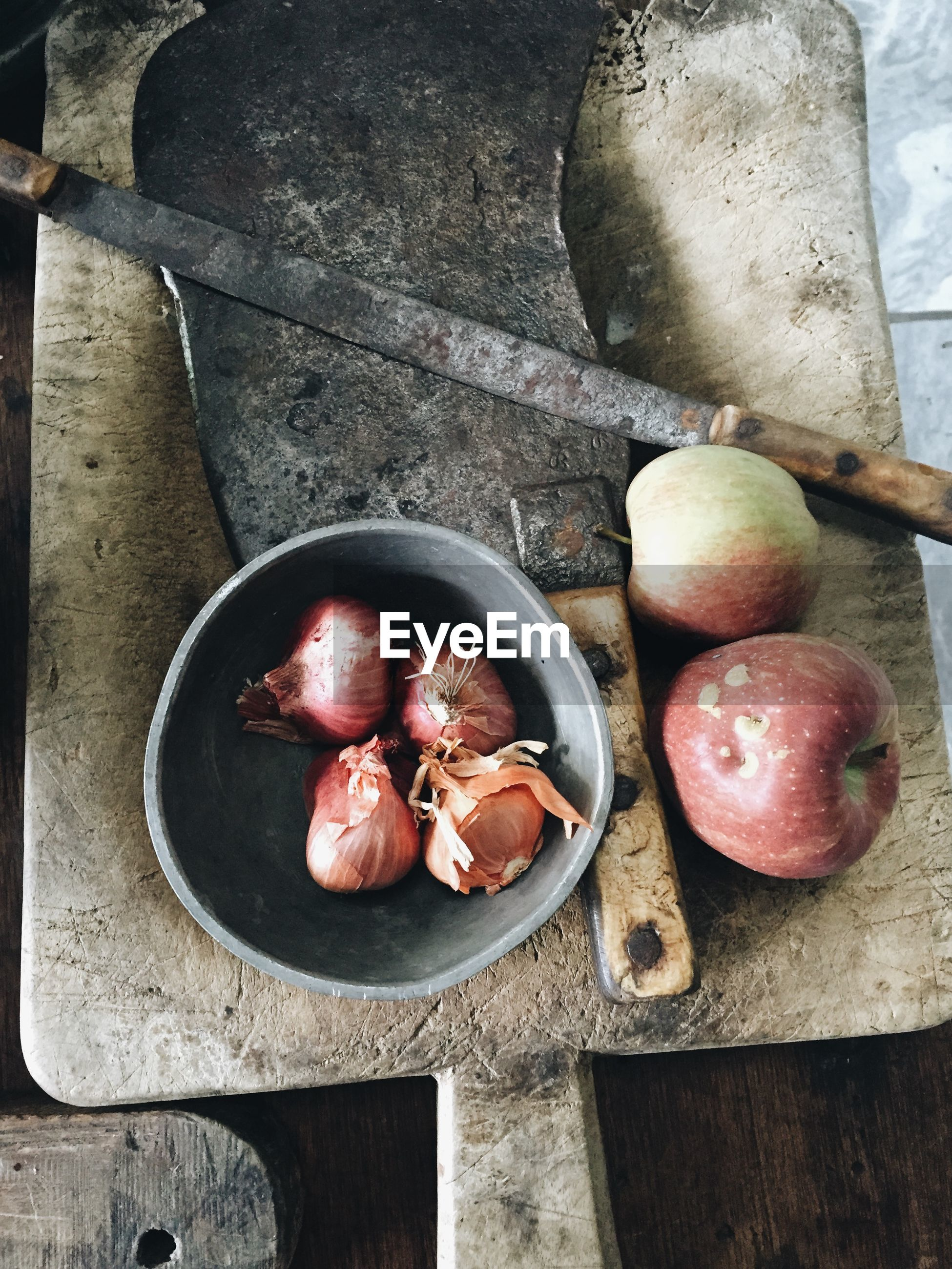 Directly above view of onions and apples with knife on cutting board