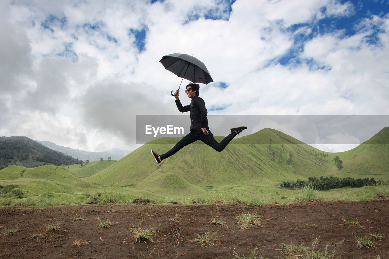 Man Holding Umbrella While Jumping On Field Against Mountain