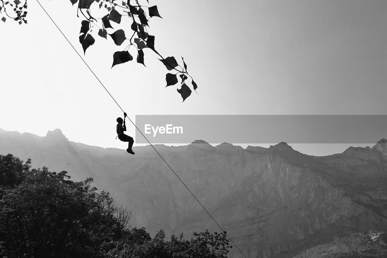 Low angle view of person rappelling on rope against mountains