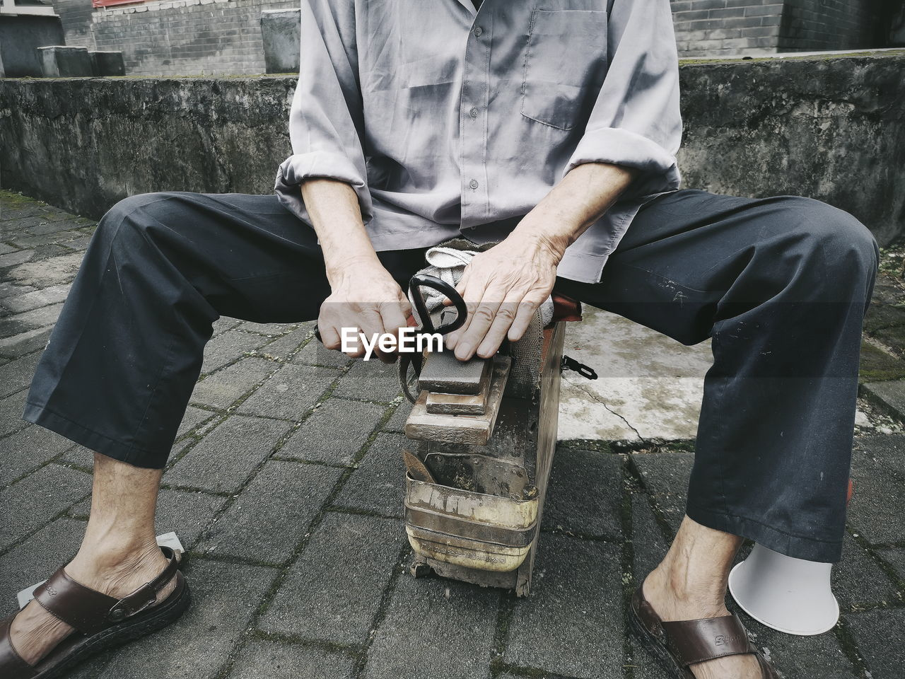 Low section of man sitting on equipment at street