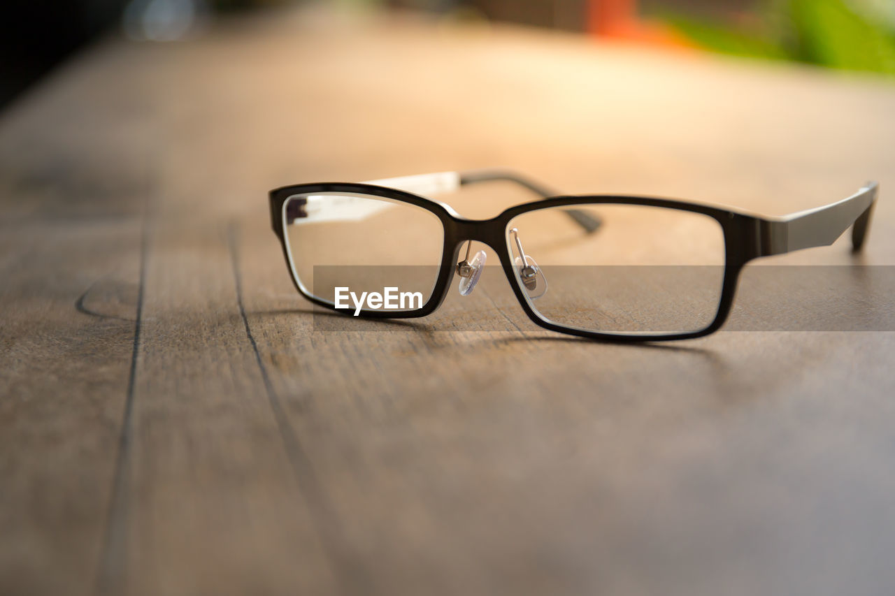 glasses, eyeglasses, table, selective focus, close-up, still life, no people, personal accessory, eyesight, indoors, eyewear, wood - material, glass - material, vision, single object, transparent, day, black color, sunlight, surface level