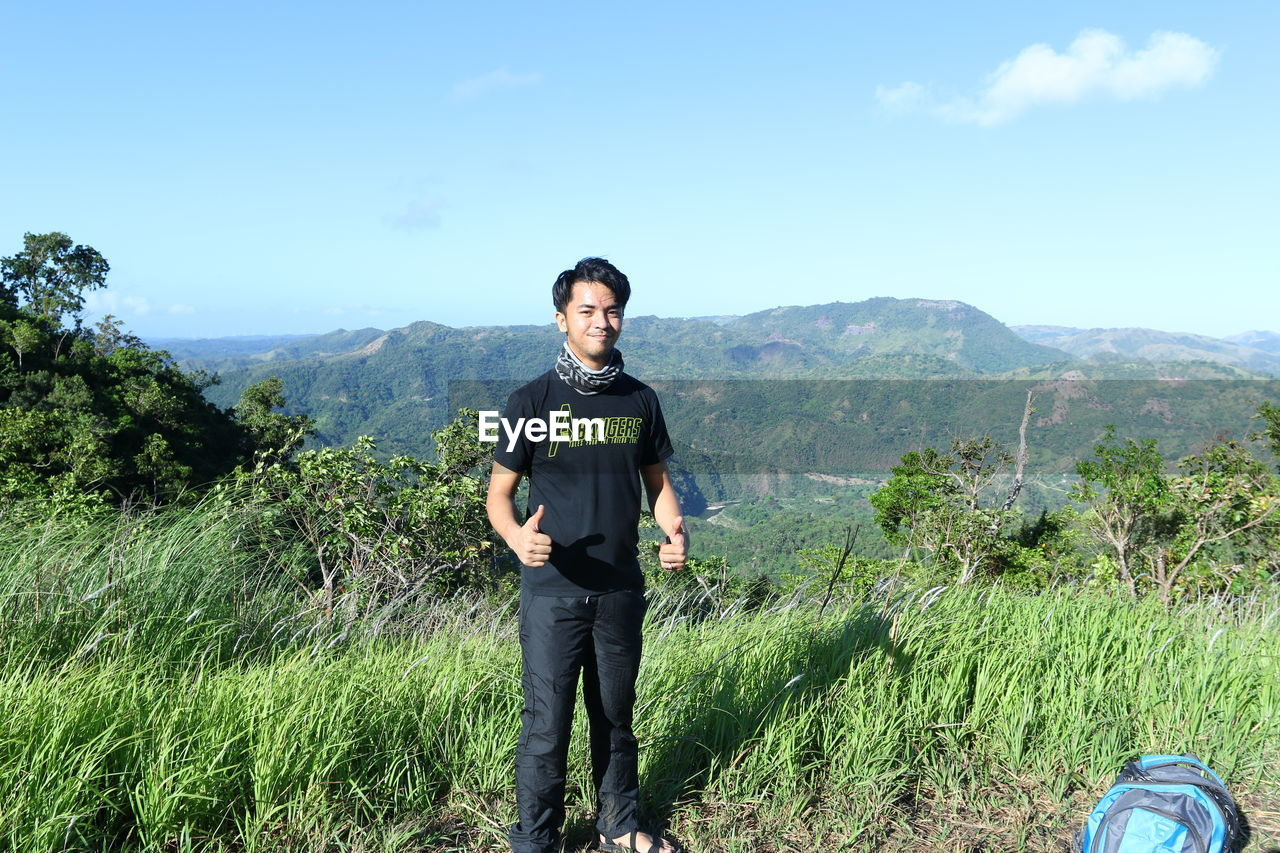 real people, mountain, nature, one person, beauty in nature, casual clothing, standing, day, sky, front view, leisure activity, backpack, mountain range, lifestyles, hiking, adventure, scenics, full length, tree, landscape, green color, grass, field, looking at camera, outdoors, young adult, young men, growth, plant, forest