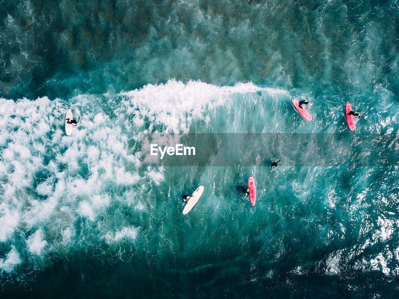 Aerial view of people surfboarding on sea
