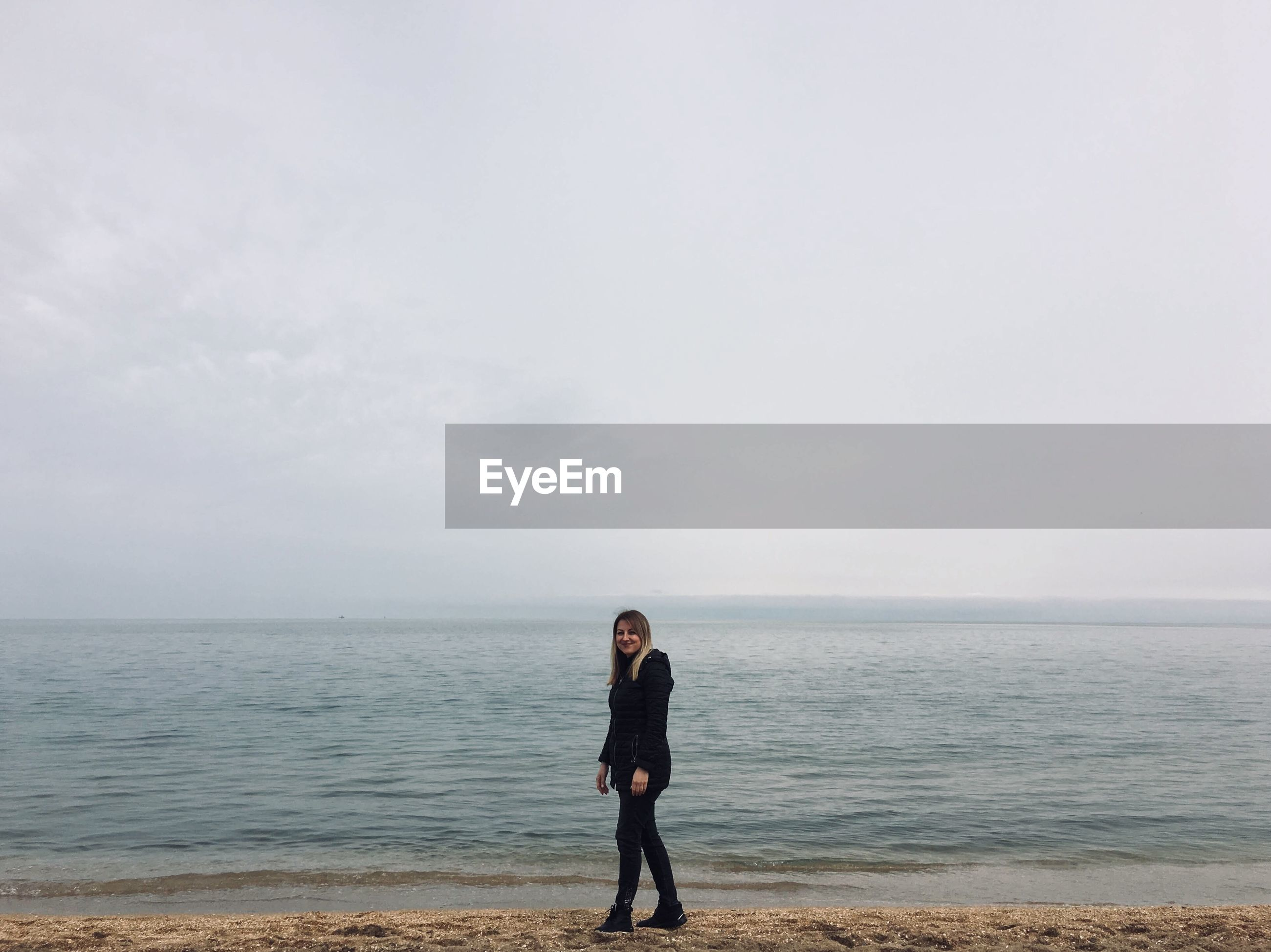 Full length of woman walking on shore at beach against sky