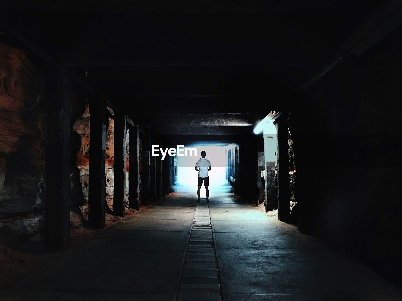 Full Length Rear View Of Man Standing Inside Tunnel