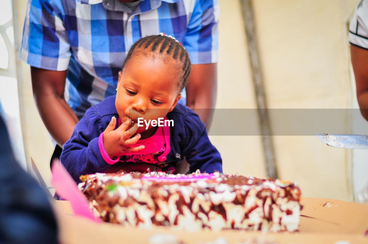 Girl Licking Birthday Cake At Home