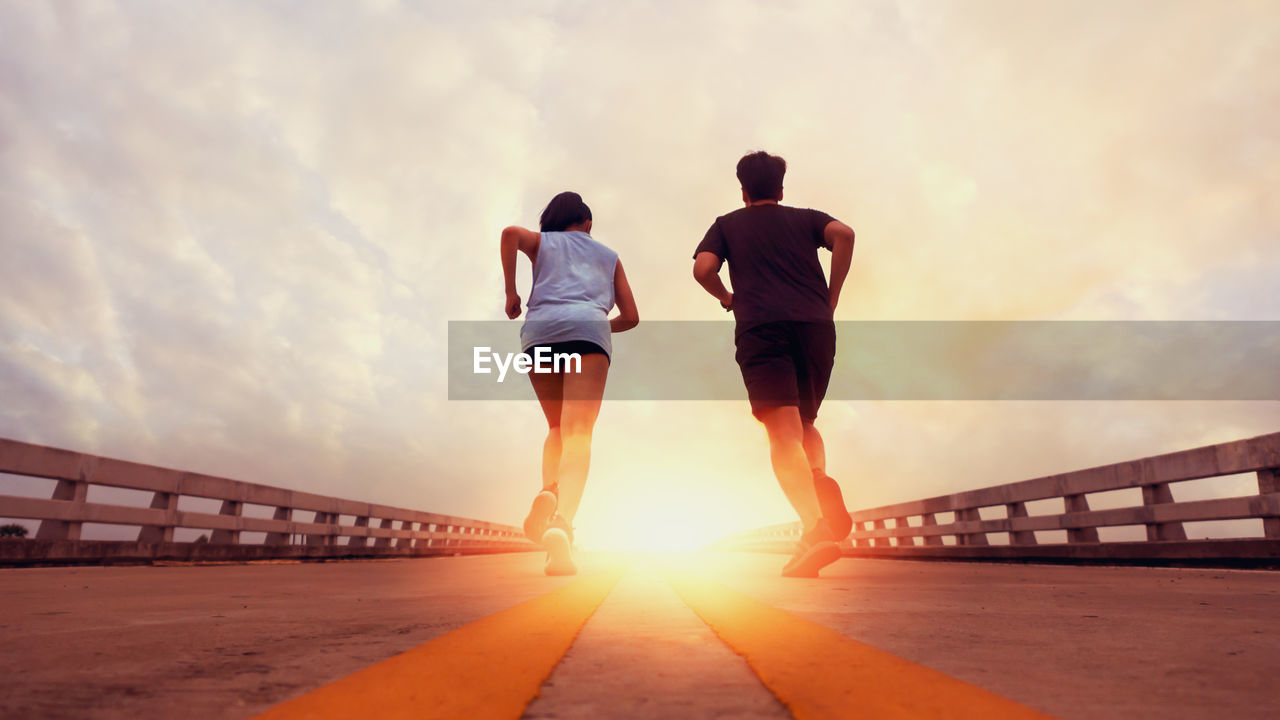 sky, sunset, rear view, lifestyles, men, bridge, real people, built structure, architecture, nature, leisure activity, full length, cloud - sky, women, sunlight, two people, people, adult, bridge - man made structure, railing, outdoors, sun, lens flare, couple - relationship