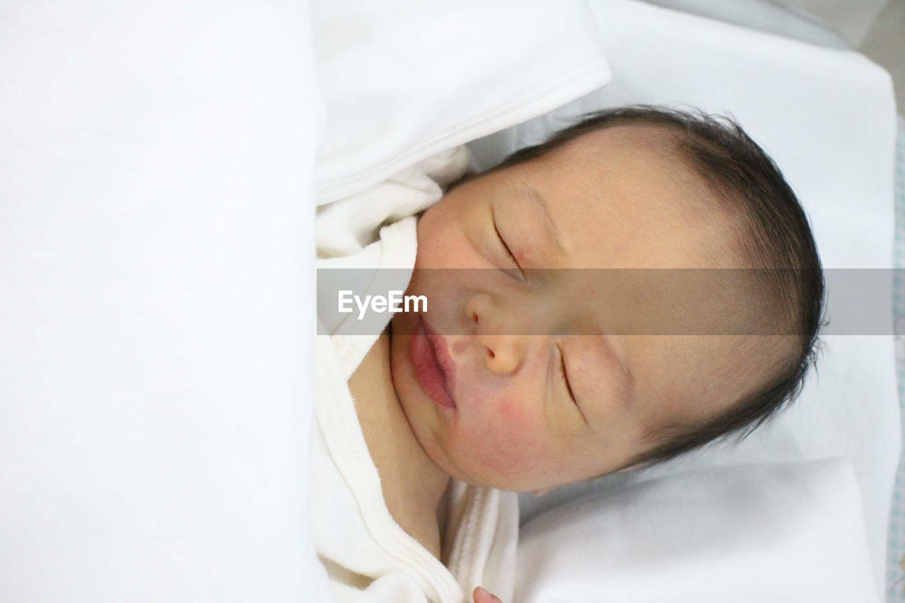 PORTRAIT OF BABY SLEEPING IN BED