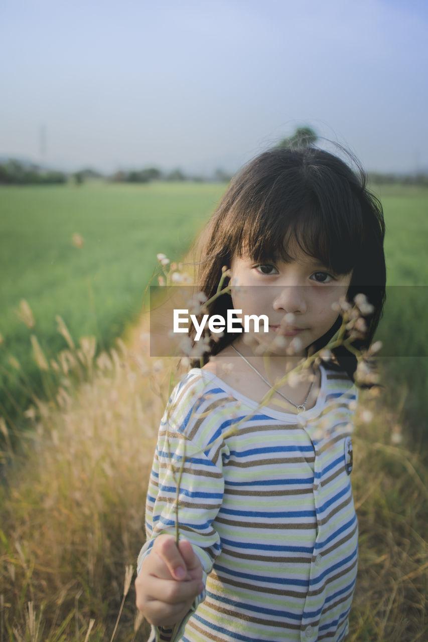 Portrait of cute girl standing on grassy field against sky