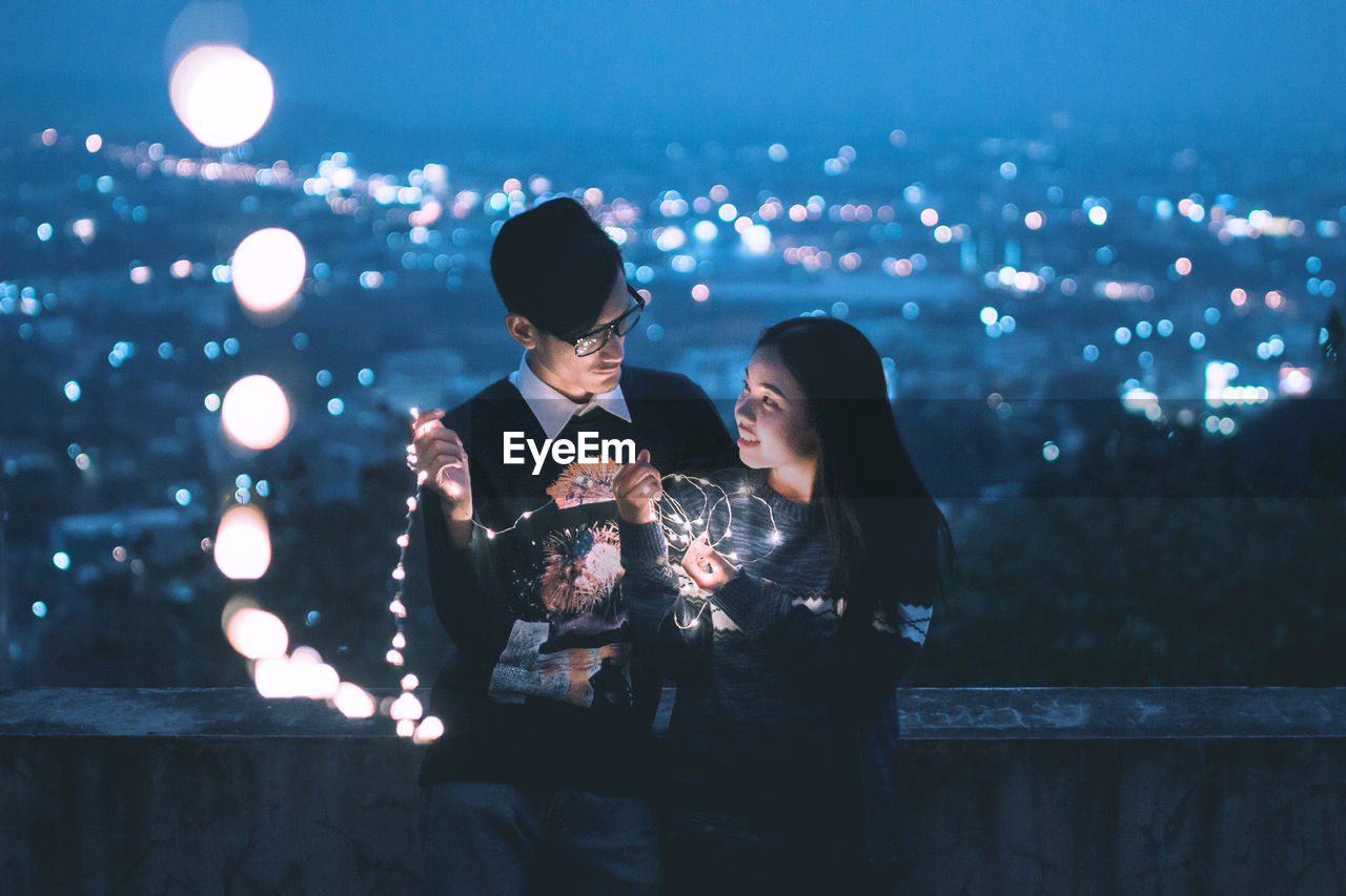 Couple Holding Illuminated String Lights While Standing In Terrace At Night