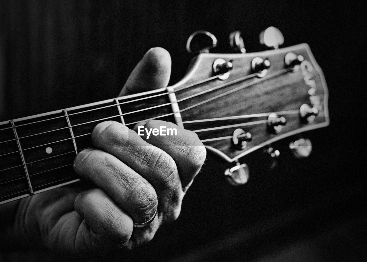 Cropped hand of man playing guitar