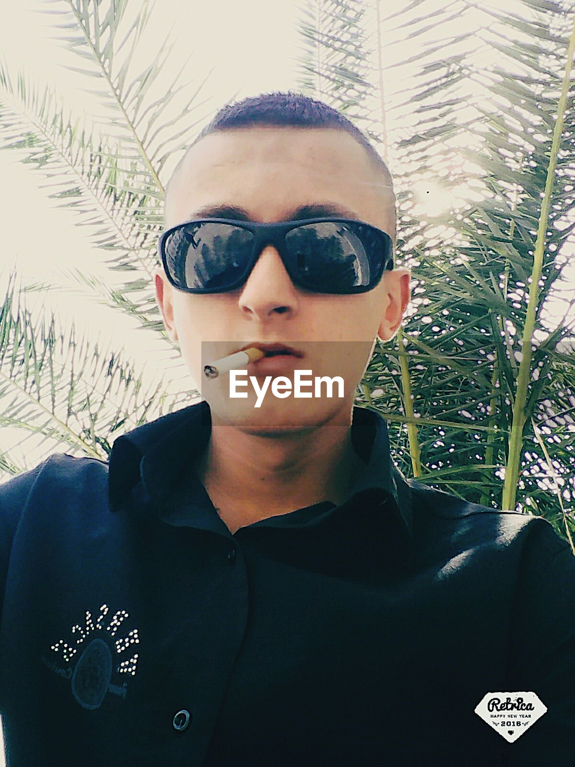 sunglasses, young adult, lifestyles, leisure activity, young men, looking at camera, person, headshot, portrait, front view, communication, eyeglasses, photography themes, wireless technology, photographing, head and shoulders, technology