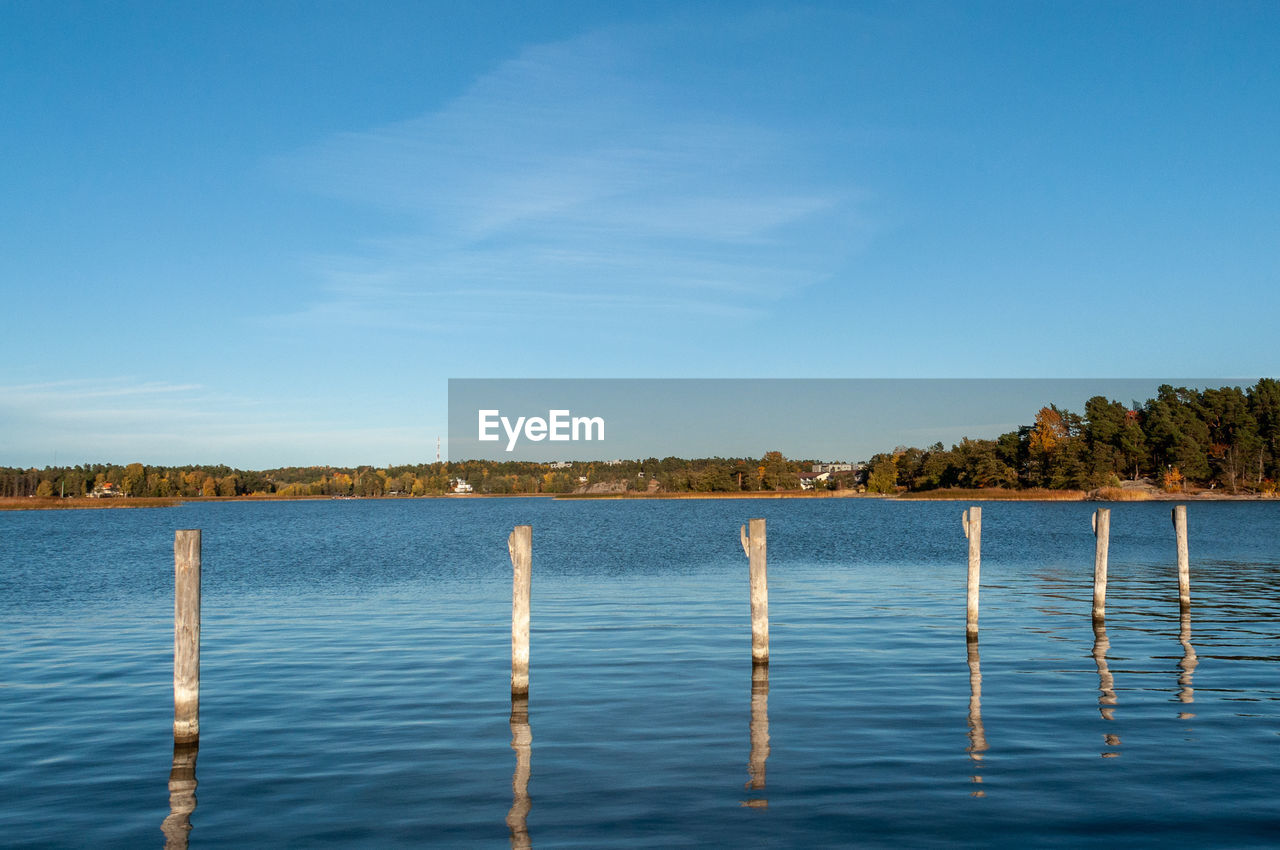 WOODEN POST IN LAKE AGAINST BLUE SKY