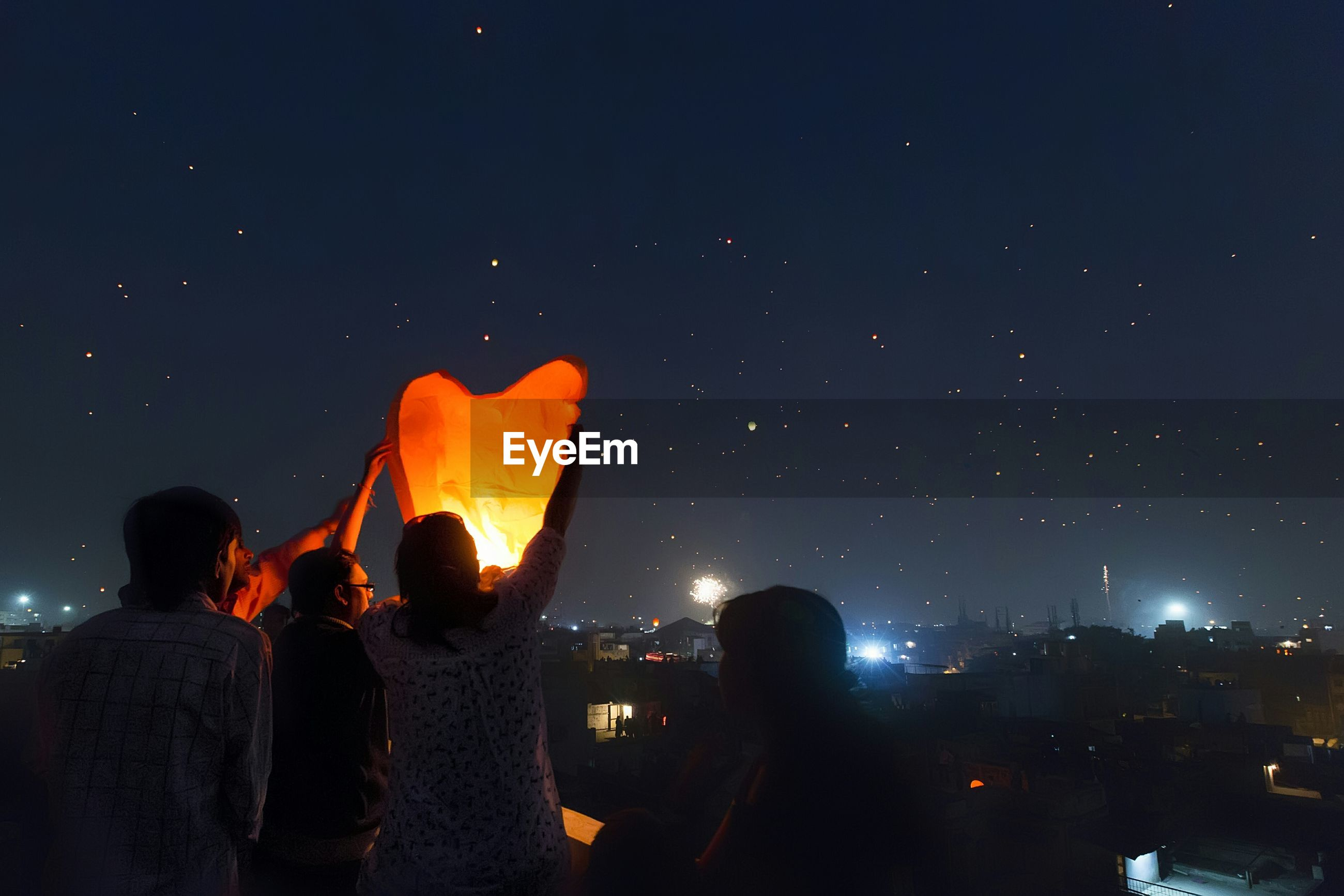PANORAMIC VIEW OF CROWD AT NIGHT AGAINST SKY