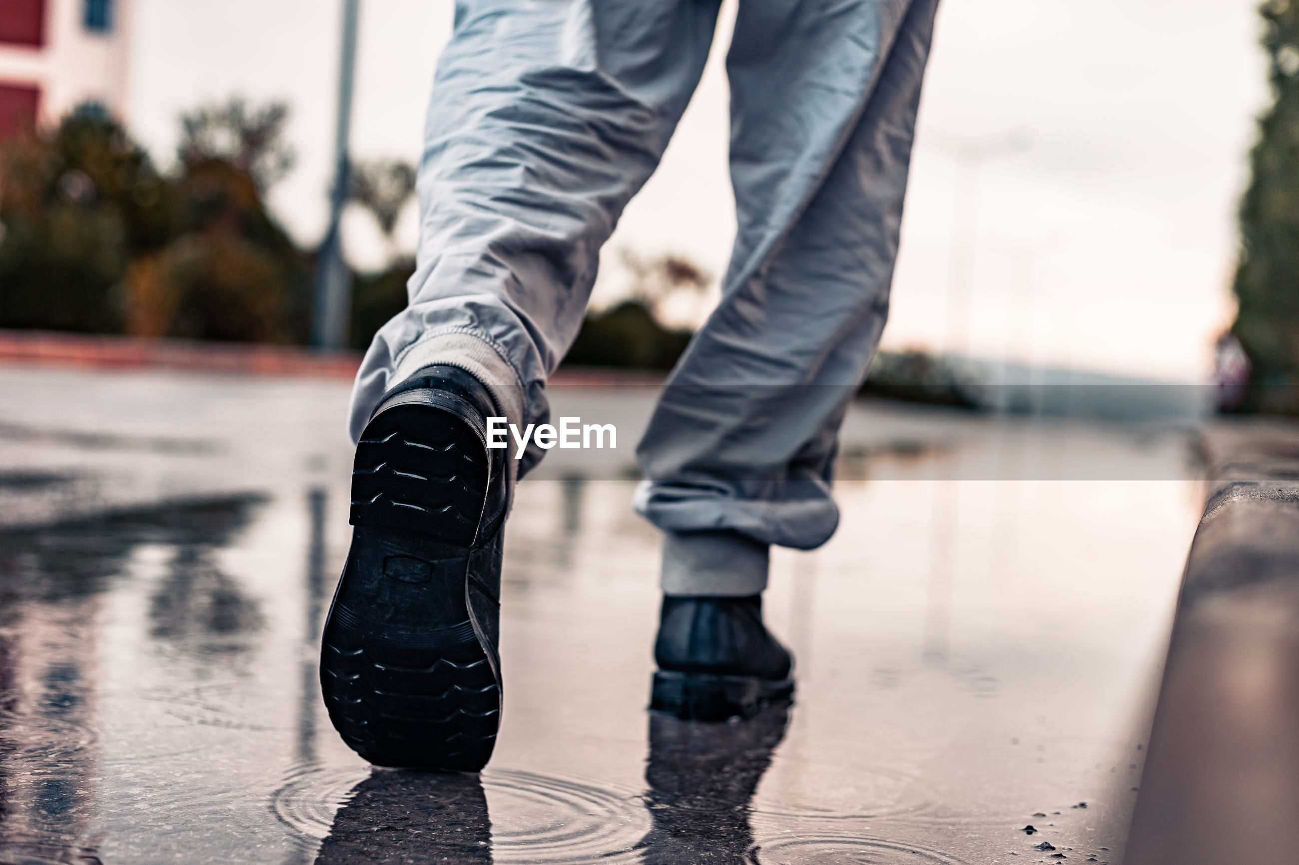 Low section of man walking on wet road during rainy season