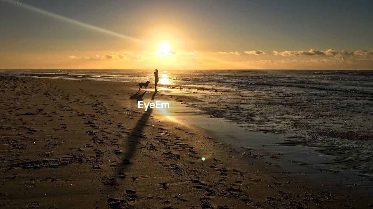 sunset, beach, sky, land, sea, water, beauty in nature, scenics - nature, horizon over water, horizon, sand, sunlight, sun, real people, orange color, nature, tranquility, silhouette, leisure activity, outdoors